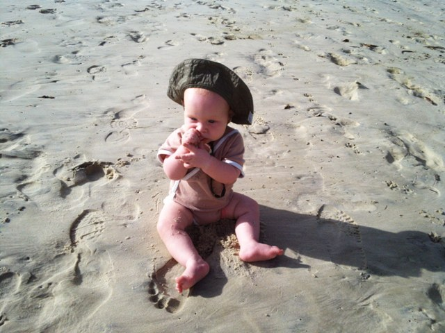 the baby eating sand